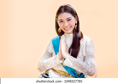 "asian girl in thai vintage costume siting and greeting action on brown silhouette thai hose background. Greeting with hand in Thai tradition call ""Sawasdee""."