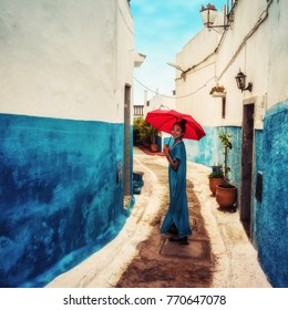 Asian Girl in Traditional Moroccan Dress with a Red Umbrella in the Blue Kasbah of Tangiers, Morocco