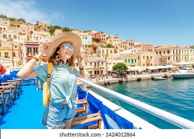 Asian girl traveler with backpack and hat enjoys a sea cruise on a open ship deck. Tourism and vacation in Greece and mediterranean sra. Transport and travel inspiration