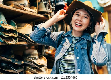 asian girl traveler trying trilby in the cowboy shop in pier 39 san francisco. young female backpacker cheerfully face camera smiling wearing hat. travel in usa experience american historical lifes.