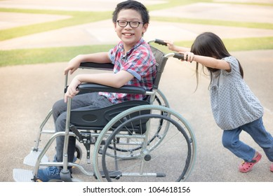 asian girl try drive a wheelchair of her brother, family time