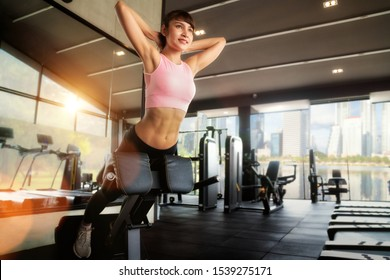 Asian girl use a stomach exercise equipment in indoor fitness gym for sit up and make six pack, this photo can use for sport, healthy and training concept