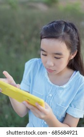 asian girl use tablet pc at park.