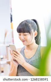 An Asian girl uses a smart phone in her room. Talking on the phone. Internet of Things. Communication technology.