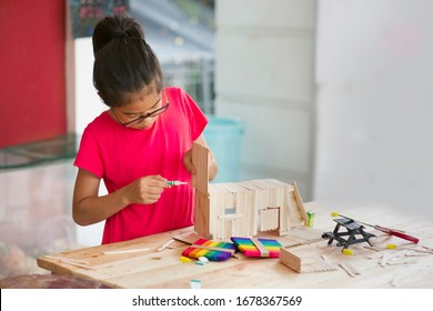 Asian girl using glue to fix popsicle sticks project. Child crafting using sticks.Young female homeschooler making craft using wooden stick on table in outdoor.Mini picnic bench.Homeschooling.