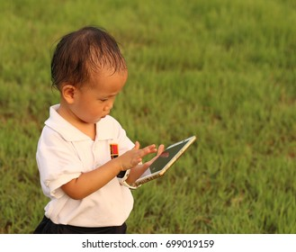a Asian girl using smart phone on a meadow