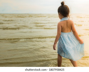 Asian girl walking on the beach in the evening