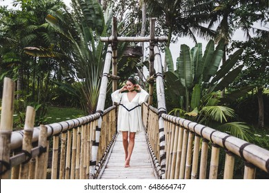 Asian girl walking on suspension bamboo bridge in Ubud Bali. Luxury villa in Canggu around green tropical garden.