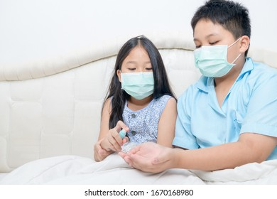 Asian girl wear hygienic mask and press alcohol spray to hand's brother for protect Wuhan coronavirus and epidemic virus. Coronavirus or covid-19 concept