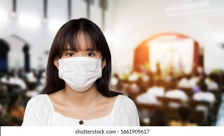 asian girl wear a white hygienic mask and blurred image of crowd people in the church