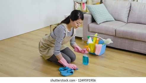 asian girl wearing apron kneeling down on the wooden floor sweeping. young housewife holding cloth and spray cleaning up the room. lady doing housework at home lifestyle concept.