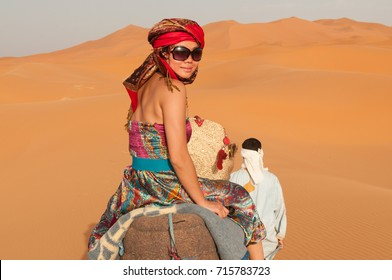 Asian girl wearing colourful clothes, a head scarf and harem pants riding a camel across the Sahara Desert in Morocco, North Africa, turns back to look at the camera.