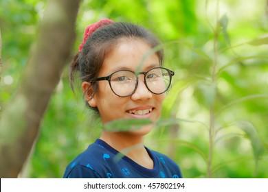 Asian girl wearing glasses in the garden