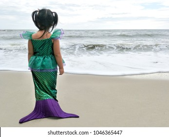 Asian girl wearing green mermaid standing by the sea.
