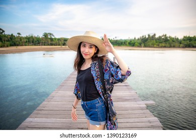 Asian girl wearing hat smiles and standing on the pier beach at Ao Tan beach, Koh Mak island, Trat, Thailand