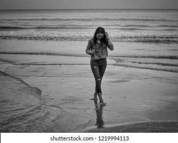 Asian girl wearing jeans is holding a camera and walking on the beach.
