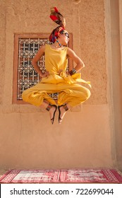 Asian girl wearing sandals, sunglasses, a yellow dress and a red turban jumps on a carpet with her hands on her waist, in the Western Sahara Desert, Morocco, North Africa.
