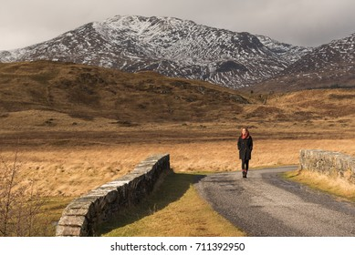 Asian girl wearing a scarf and black walks on a road near the Bridge of Orchy, Argyll and Bute, Scotland, UK, where snowy mountains can be seen on the background, and a tree on the foreground.