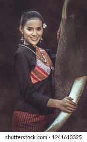 Asian girl wearing traditional silk dress. She is hugging elephants.