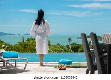 Asian girl wearing a white bathrobe take a look at the sea and the blue sky atmosphere is very happy.