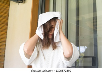 Asian girl wearing white bathrobe Show skin clean.Attractive female wipes wet hair with towel, wears white bathrobe, going to make hairstyle, prepares for special occasion, wants look beautifully.
