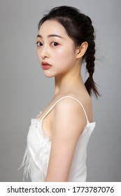 Asian girl wearing white costume in gray background