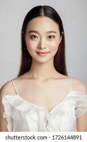 Asian girl wearing white dress in gray background