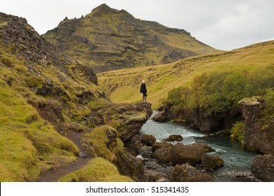 An Asian girl wearing a woolly hat and wellington boots stands on the edge of a rock admiring the magnificent view of the river running through the valley near the Skogafoss Waterfall , Iceland.