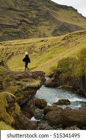 An Asian girl wearing a woolly hat and wellington boots walks away from the edge of a rock with views to a river running through the valley near the Skogafoss Waterfall , Iceland.