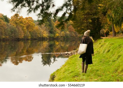 Asian girl wearing a wooly hat, wellington boots and carrying a bag walks near the calm waters of the River Tummel in Pitlochry, Perthshire, Scotland, UK, glancing at the beautiful autumn colors.