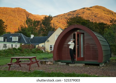 An Asian girl wearing a wooly jumper adjust her wooly hat with her hands while stretching in a cold morning beside a cabin Pod in Clovullin, Fort William, where hills can be seen on the background.