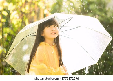 Asian girl wearing yellow raincoat and enjoying rainfall in the park. Kid playing on the nature outdoors.