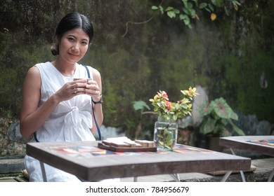 Asian girl in white dress drinking tea in the garden with wooden table and rustic cement wall background to relax on vacation time , asian woman holiday portrait