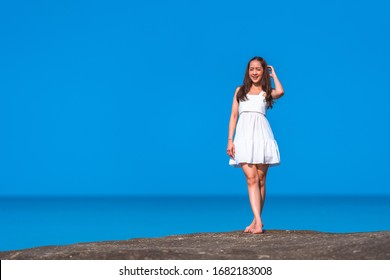 asian girl in white dress a holiday relax time in white dress by standing on stone on the sea with sunday light and blue sky in relaxing and freedom concept