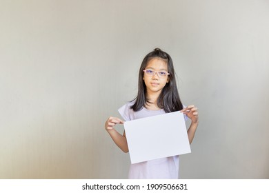 Asian girl with white sheet of paper, girl holding empty blank paper, mock up blank sign for message creative design concepts.