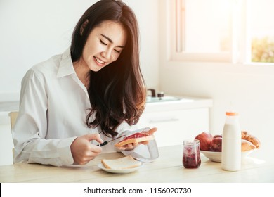 Asian girl who just wake up in the morning as relaxed. She opened the window to receive the light of the morning sun. She was making the bread and strawberry jam.