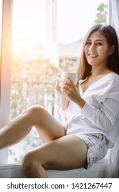 Asian girl who just wake up in the morning as relaxed. She opened the window to receive the light of the morning sun. She was holding a cup of coffee or tea to drink it.