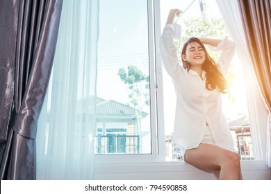 Asian girl who just wake up in the morning as relaxed and smiling. She opened the window to receive the light of the morning sun.