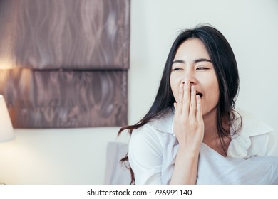 Asian girl who just wake up in the morning as relaxed and smiling. She opened the window to receive the light of the morning sun. She is yawning with sleepiness.