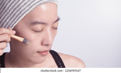 Asian girl or woman 40 years old beautiful face with japanese look making up by foundation liquid and cosmetic brush on sensitive skin for helping her complexion look flawless and real no retouch