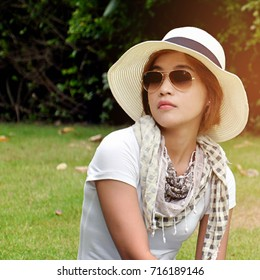 Asian girl or woman closing eyes sitting on grass field in the garden wearing sunglasses, scarf, hat and white T-shirt in relaxing posture.
