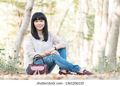 Asian girl in the woods. There are many pines and plants in the woods.