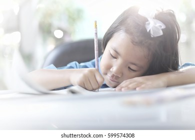 Asian girl writing a book, selective focus and toned image. Signed model release.