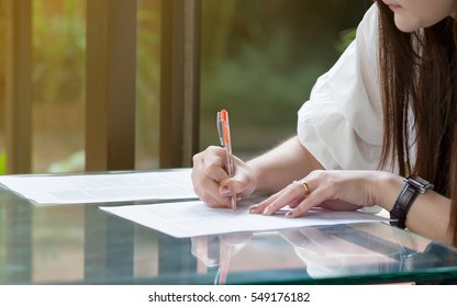 Asian girl writing paper on the table in the room.