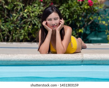 Asian girl in yellow bikini takes the sun and interacts with her mobile phone next to a swimming pool