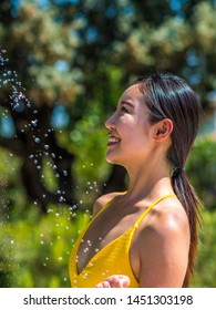 Asian girl in yellow bikini takes a shower by the pool