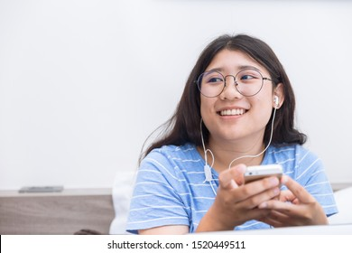 Asian girl young teen student using smartphone listening music happy smile relax on ben at holiday