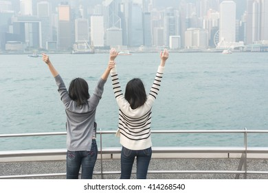 Asian girls feel free and stand at the Victoria harbor, Hong Kong, Asia.