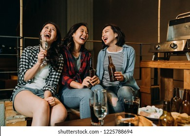 asian girls having fun chatting on barbecue party on roof at night. young ladies sitting chill out on holidays drinking alcohol beer champagne and wine. friends laughing talking about funny things.