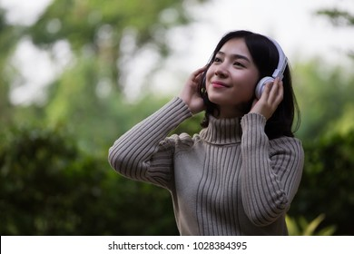 Asian girls are listening to music in the park.